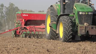 farmer-on-farmland-with-tractor-and-sower-sow-cereal-crops-closeup-4k_hpokn1ax__S0000